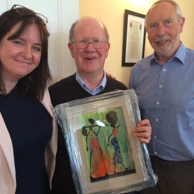 Jenni Barrett, chief executive, and John Cooley, chair of the Board, present a painting from Kenya to Br. Pat Madigan, Community Leader of Edmund Rice House, on the occasion of his retirement.